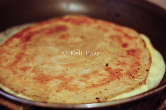 Add the paratha over the egg..