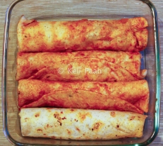 Rolled up tortilla's... the odd one out is the one which has not been dipped in the sauce before heating..