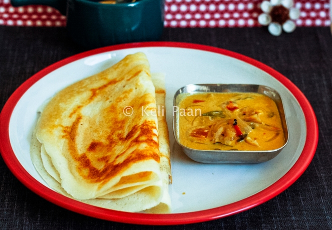 Serve the Takkali Kolumbu with hot Dosa's..