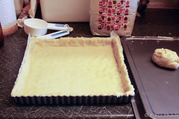 Transfer the rolled pastry sheet to the tin lined with greaseproof paper..