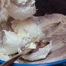 Strain the sweetened yogurt using a sieve..